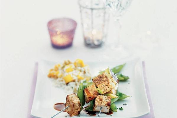 tofu skewers with soy sauce on a bed of sugar snaps