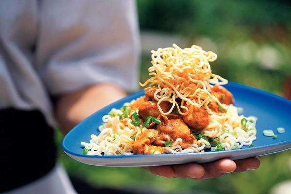 chicken in red coconut curry with cooked and fried noodles