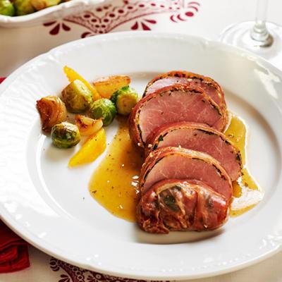 pork tenderloin wrapped in fresh herbs and raw ham
