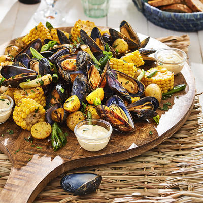 mussel board with corn and potatoes in the shell