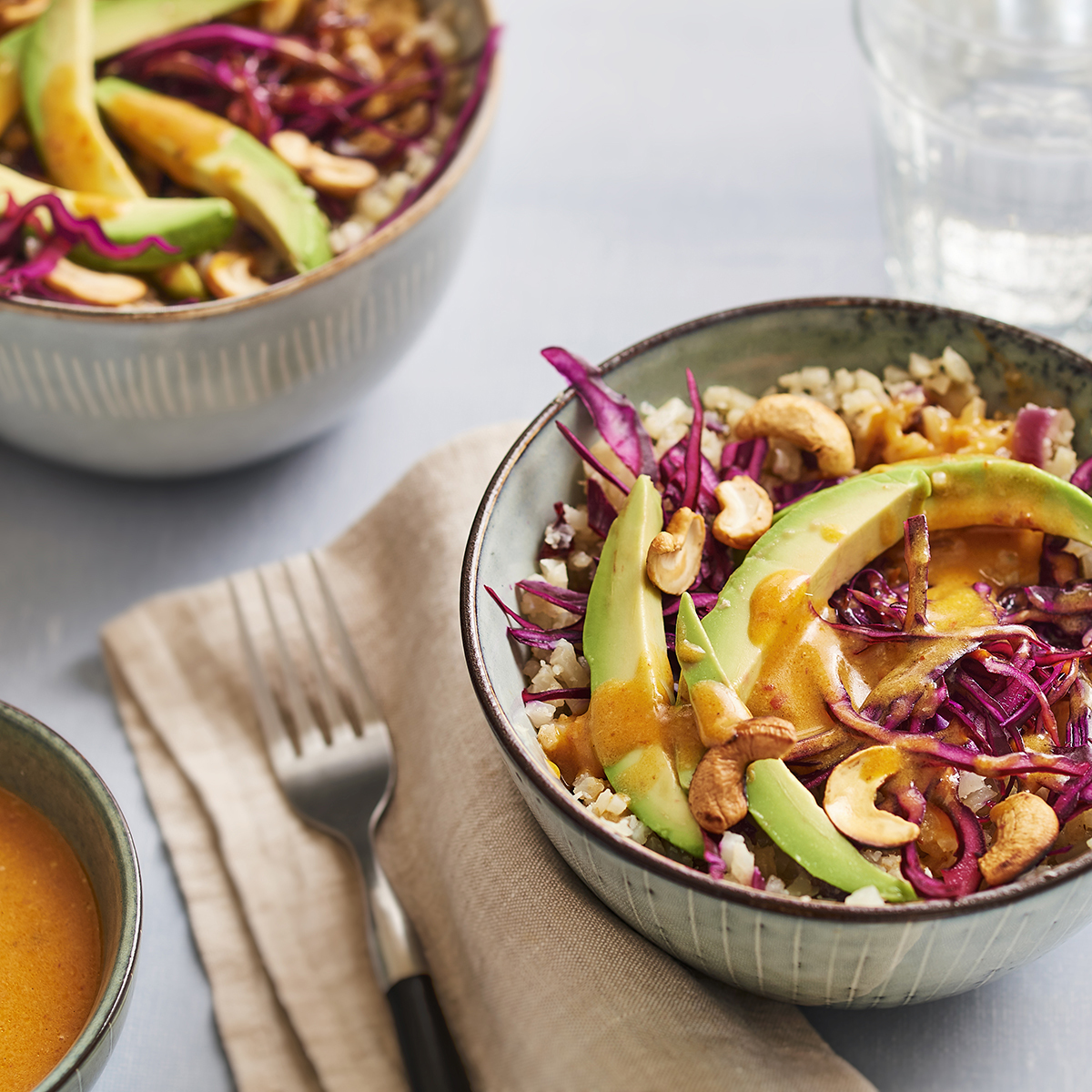 Bowl with cauliflower rice, avocado, red cabbage and cashew nuts