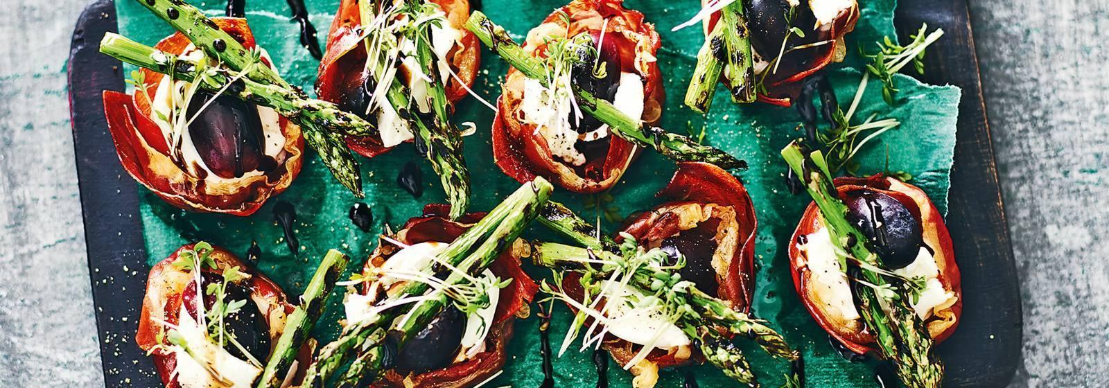 Crunchy prosciutto cakes with asparagus tips and buffalo mozzarella